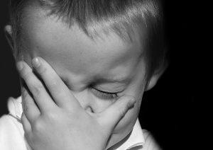 a little boy in grief cries