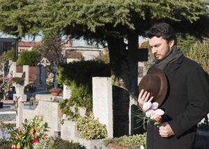 a man grieves for his child at a cemetery