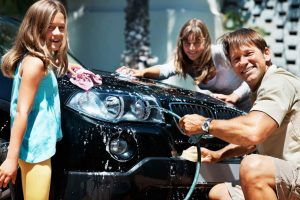 a dad spends quality time with his daughters washing the car