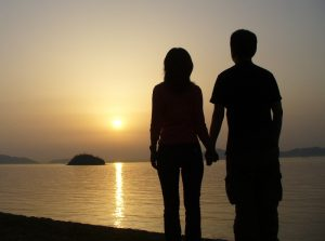 happy couple holding hands at sunset on a beach can benefit from marriage counseling