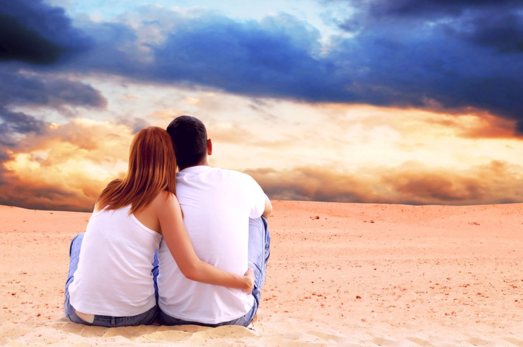 shutterstock 83356945 happy couple seating sunset beach 1024x680 1
