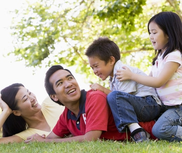 family lying outdoors being playful and smiling HFnwKRBi